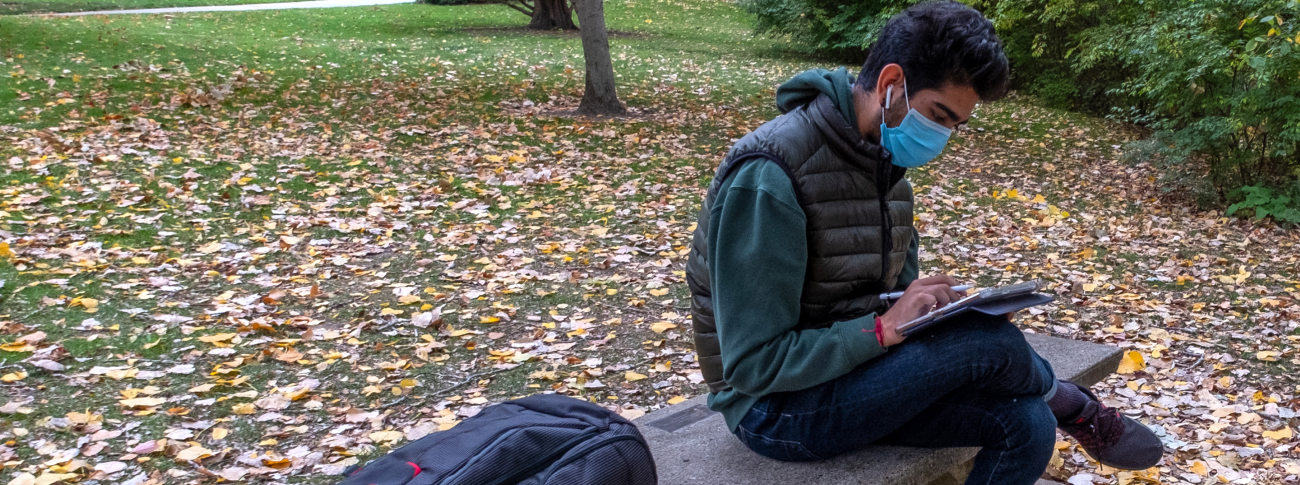 Student studying outside on a bench, wearing a mask